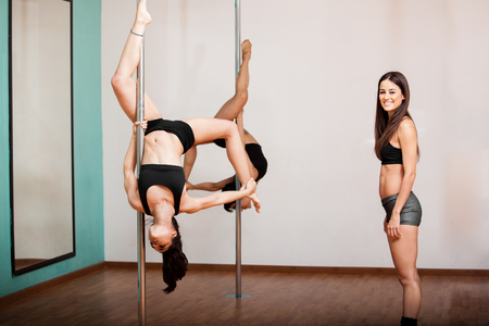 supervision: Happy pole fitness business owner in front of a pair of women working out