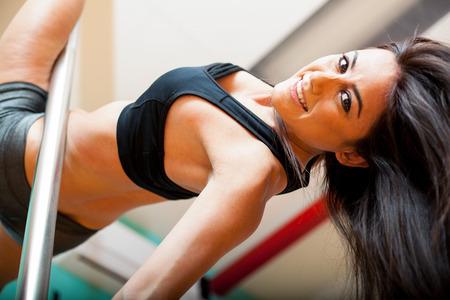 mujeres fitness: Bailarina de barra atractiva y hermosa que cuelga detr�s de un poste y sonriendo bajo el �ngulo de visi�n