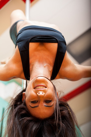 Beautiful young woman hanging upside down from a pole and smiling photo