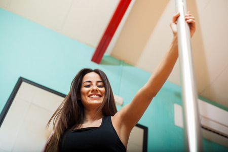 striptease: Beautiful young woman ready for her pole fitness class and smiling  Low angle of view