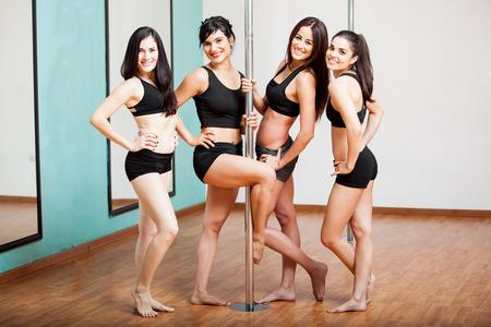 pole dance: Gruppo di belle ragazze che colpisce una posa e divertirsi durante una lezione di fitness pole Archivio Fotografico