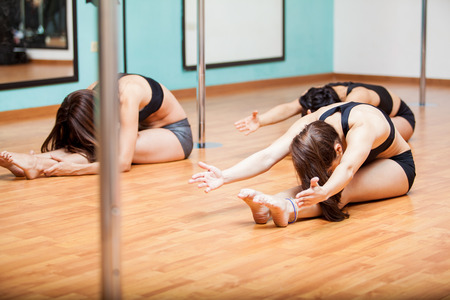 sexy girl dance: Group of young women stretching and warming up on the floor for their pole dancing class Stock Photo