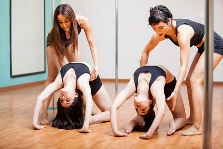 Cute pole dancing students working on their flexibility with the help of a couple of instructors photo