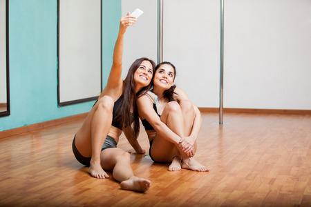 mujeres fitness: Joven y bella mujer tomando una selfie durante un descanso en una clase de gimnasia polo