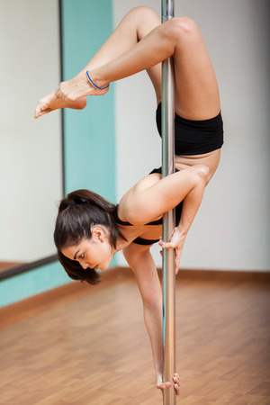 Sexy and strong young woman working out during a pole dancing class at a gym