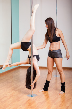 Cute pole fitness instructor helping a student with her technique photo