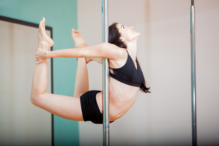 pole dance: Cute Hispanic young woman working out in her pole fitness class Stock Photo