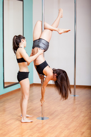 Couple of beautiful young pole dancers assisting each other during practice photo