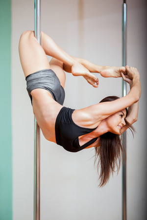 Cute and athletic Hispanic woman enjoying her pole dancing practice  Low angle of view Zdjęcie Seryjne