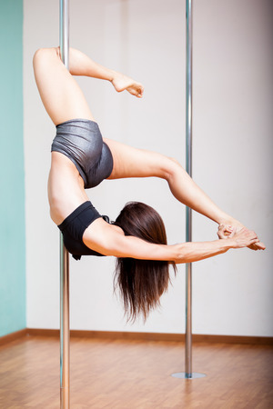 Portrait of a beautiful and athletic brunette pole dancing