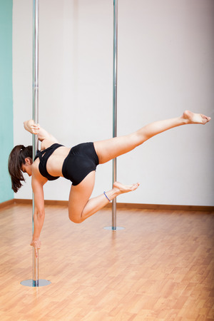 Young woman working out in a pole fitness class photo