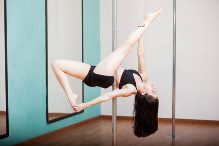 Pretty Hispanic pole dancer working on a new pose at a gym photo