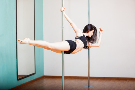 Gorgeous young woman practicing the superwoman pose during her pole fitness class