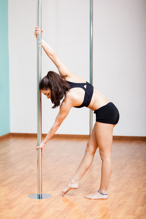 Cute young woman going up on a pole during pole dancing practice