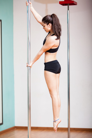 Beautiful Latin young woman working on her strength during pole fitness class