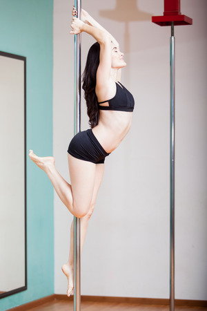 pole dance: Happy young woman working out and enjoying her pole dancing class