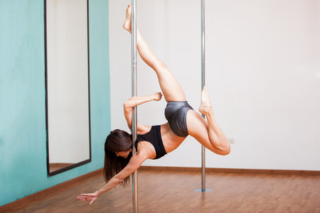 sexy girl dance: Beautiful young woman showing off her strength and balance while pole dancing Stock Photo
