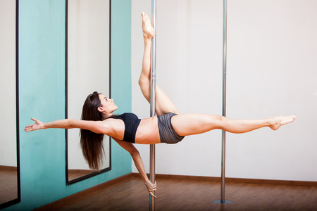 Pretty Hispanic brunette working out in a pole fitness class photo