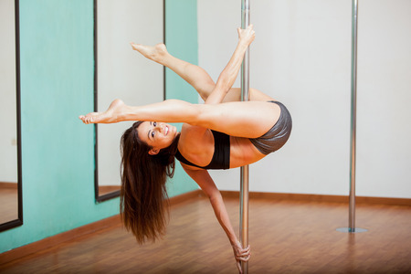 pole dance: Cute young Hispanic woman trying a pole dancing routine and smiling Stock Photo