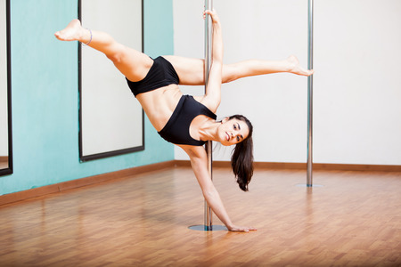 Sexy and skillful pole dancer practicing some moves in a gym