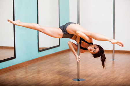 Strong and flexible young woman splitting her legs while hanging on from a pole