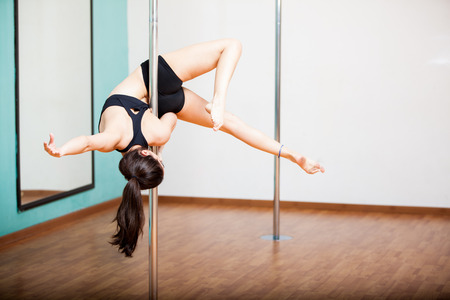 Young brunette trying a beautiful pose during a pole dancing class photo