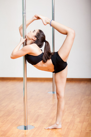 Pretty brunette stretching and warming up during her pole fitness class at a gym photo