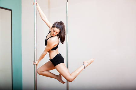pole dancing: Femme magnifique et fort la tenue d'une pose pendant un cours de pole dancing dans un gymnase Grand espace de copie Banque d'images