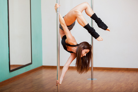 Pretty young brunette trying a new pose during her pole fitness class at a gym Zdjęcie Seryjne