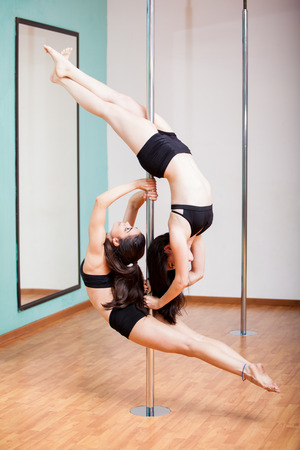duo: Gorgeous young women working together to create a beautiful pose in a pole dancing class Stock Photo