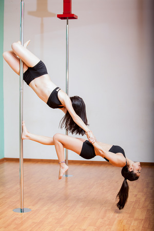 sexy girl dance: Beautiful pole dancers combining strength and balance for a beautiful routine Stock Photo