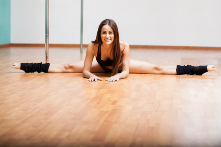 pole dance: Happy young woman stretching and doing a leg split during a pole fitness class