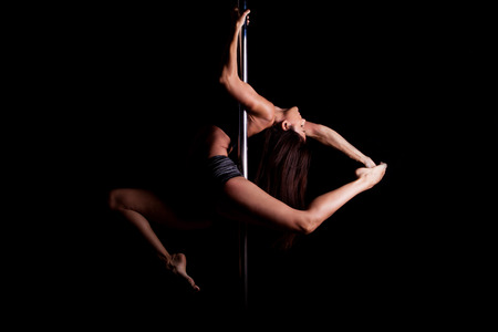 striptease women: Dramatic portrait of a gorgeous athletic pole dancer holding a pose  Stock Photo