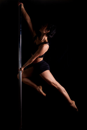 Dramatic scene of a sexy pole dancer holding a pose photo