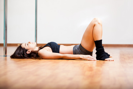 Cute young woman laying on the floor and resting during a pole fitness class photo