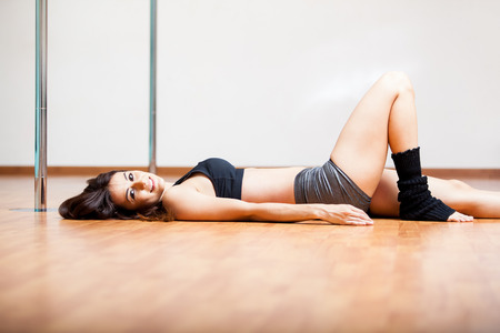 Beautiful young woman relaxing and taking a break from her pole fitness class photo
