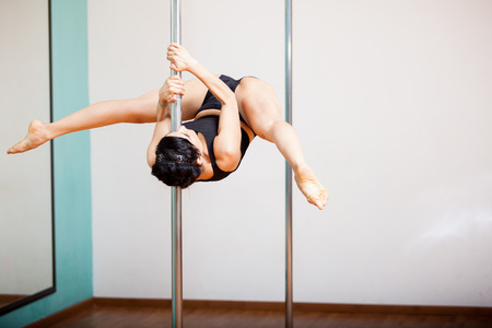 sexy girl dance: Strong Latin woman holding a pose during a pole dancing class at a gym Stock Photo