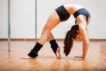 arching: Hermosa mujer joven estiramiento y arqueando la espalda en su clase de pole fitness