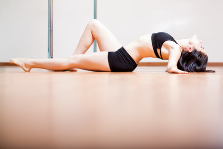 arching: Joven morena linda que pone en el suelo y arqueando la espalda durante una rutina de baile de tubo