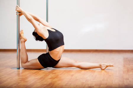Young Latin woman stretching and warming up for her pole fitness class photo