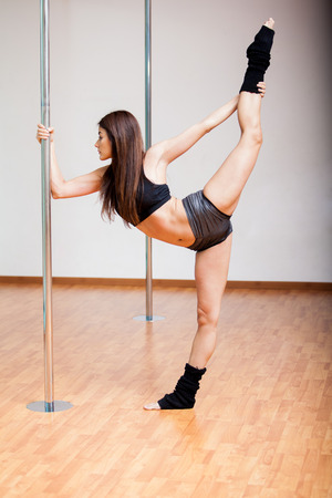 Sexy Latin pole dancer warming up and stretching before her practice photo