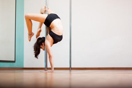 Beautiful young brunette trying a pole fitness pose at a gym  Lots of copy space