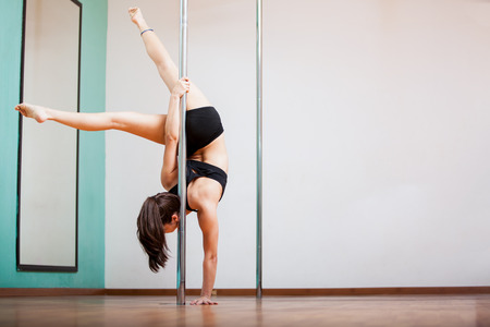 Gorgeous young brunette pole dancing in a gym  Plenty of copy space photo