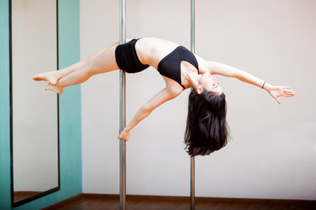 Pretty Hispanic girl holding the reverse superwoman pose in a pole fitness class photo