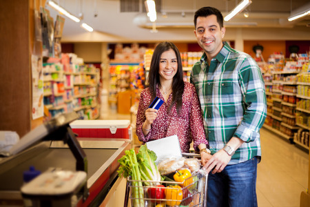 checkout: Cute happy couple paying for their food at the checkout counter with a credit card