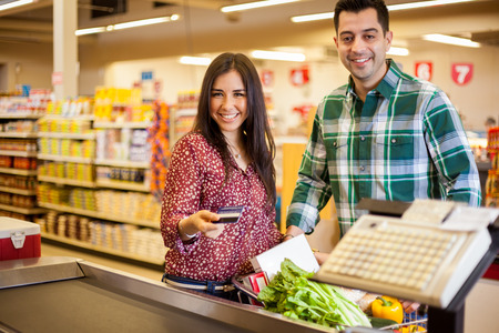 checkout: Beautiful young woman and her partner paying for groceries at the cash register with a credit card