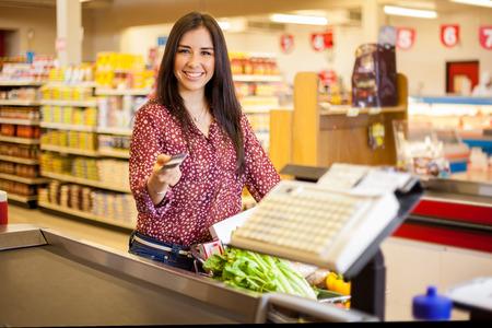 クレジット カードで支払いと笑みを浮かべてスーパー マーケットのレジで美しい若い女性
