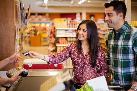 Mooie jonge brunette en haar vriend kopen van een aantal boodschappen in de supermarkt en het betalen met een creditcard