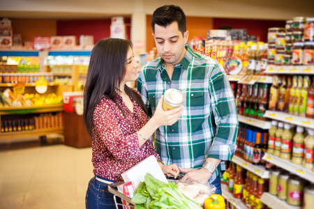 Young man and his cute girlfriend doing some shopping together at the grocery store photo