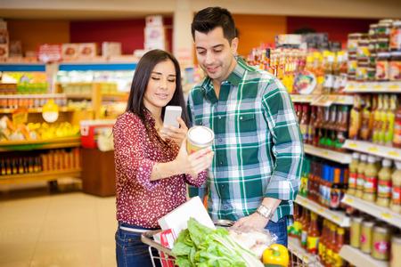tiendas de comida: Bastante joven morena y su pareja de tomar una foto de un producto con su teléfono celular en una tienda de comestibles Foto de archivo